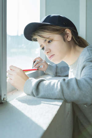 Young contractor measuring window