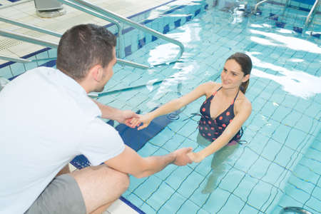 Man guiding pregnant woman in swimming pool Stock Photo