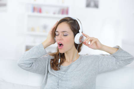Young woman singing along to music on headphones