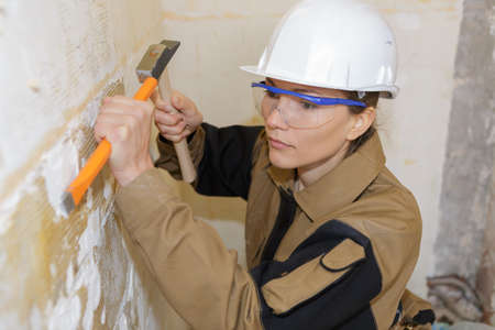 expertise: young female builder using a chisel in a construction site