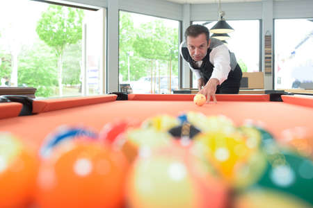 poised: Man poised to hit cue ball on pool table