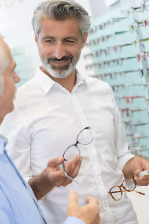 Optician passing frames to customer
