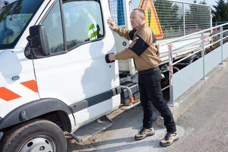 Werknemer die de deur van het voertuig sluit