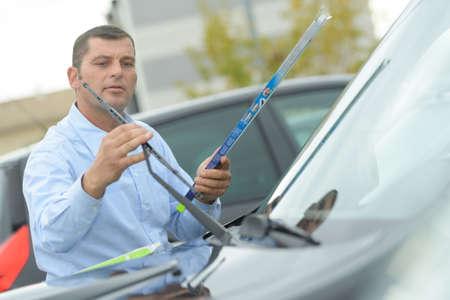 Man fitting new windcreen wiper blade
