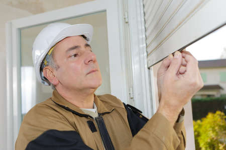 builder installing shutters Reklamní fotografie - 78772730