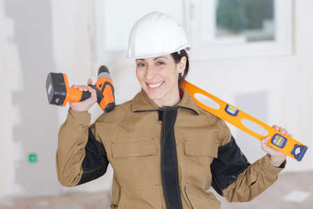 female builder with spirit level and electric drill Standard-Bild