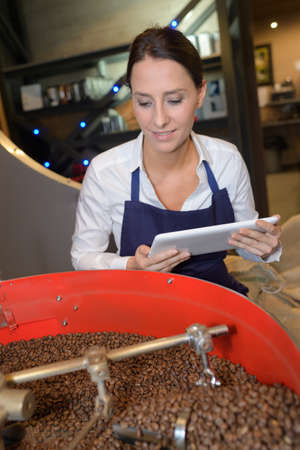 Woman holding tablet watching coffee beans being roasted