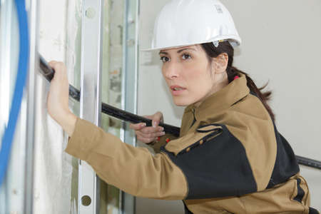 waterproofing material: female insulation worker isolating pipes in a house