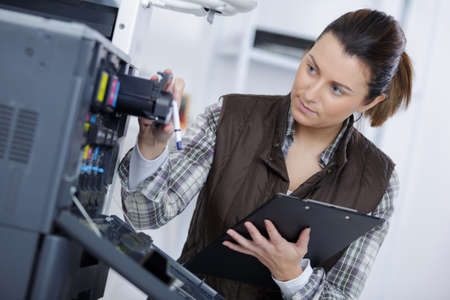 fotocopiadora: Woman inspecting office photocopier Foto de archivo