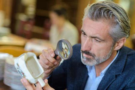 Homme regardant une cruche antique à l'aide d'une loupe Banque d'images