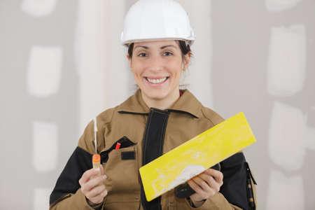 female plasterer painter portrait at indoor wall renovation