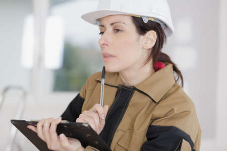 worker woman thinking while looking at clipboard Stock Photo