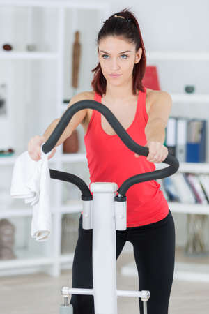domiciles: sporty determined young woman training on step machine