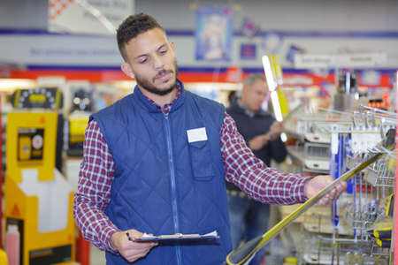 communications tools: man checking his clipboard before purchasing in a hardware-store
