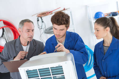 air conditioning repairmen discussing the problem with a compressor unit Stock Photo - 78817278