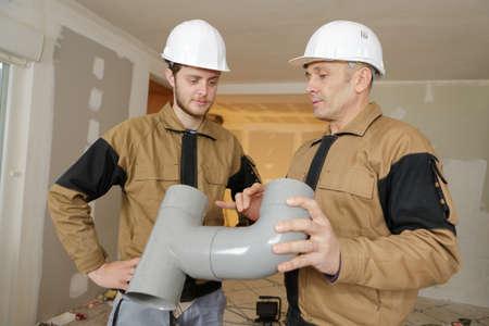 man installing plastic rain gutter system pipeline
