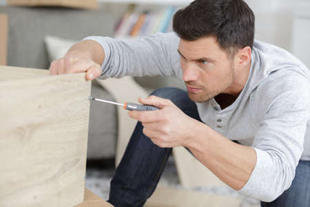 work from home: man assembles furniture wardrobe Stock Photo