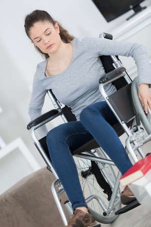 sad girl in wheelchair at home