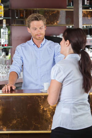 baristas: handsome waiter serving coffees to customer at the coffee shop Stock Photo