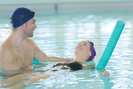 teacher and swimmer learning to swim with polyfoam roll