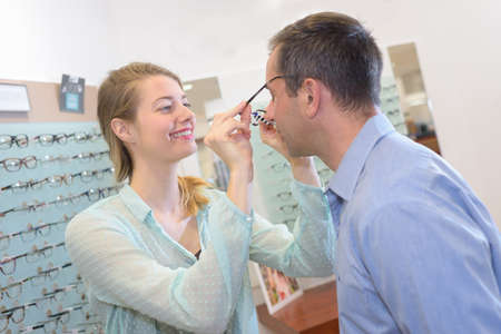 color consultation: young male client trying on glasses at optical store