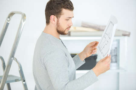 man with construction plan in new building interior