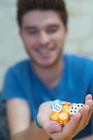 young man holding dices