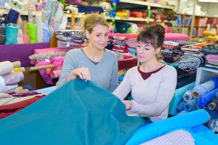 middle-aged dressmaker looking for fabrics at store