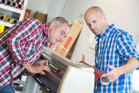 plotting: workers checking a printer format inkjet working Stock Photo