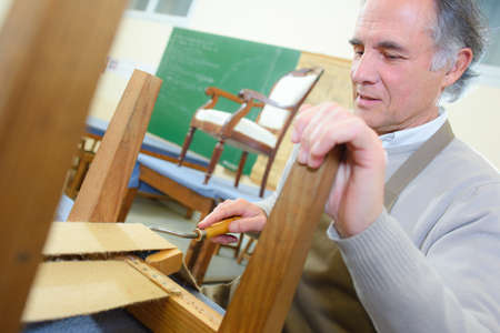 upholster: man upholstering chair in his workshop Stock Photo