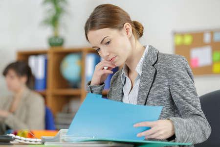 魅力的な女性の事務員は彼女のフォルダーに何かをチェックします。 写真素材