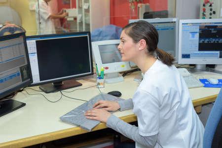 waistup: female nurse working on computer at hospital reception