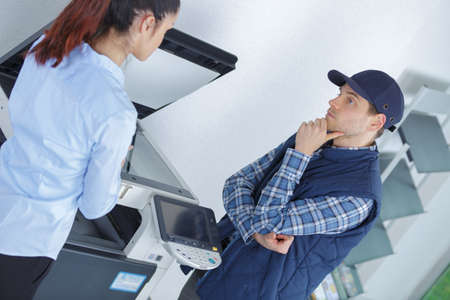 frustrated business woman opening photocopy machine in office