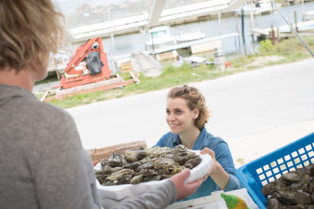 female worker delivering oysters at a fish market Stock Photo