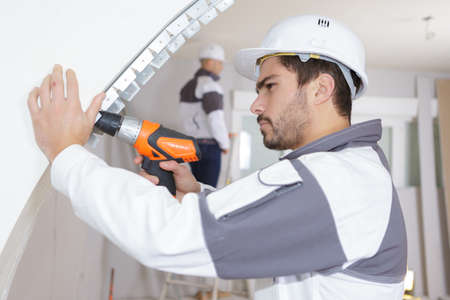 young man drilling wall indoors