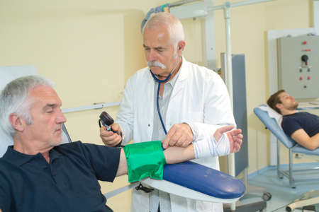 diastolic: doctor checking old man patient arterial blood pressure Stock Photo