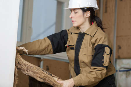 a young woman is insulating a floor
