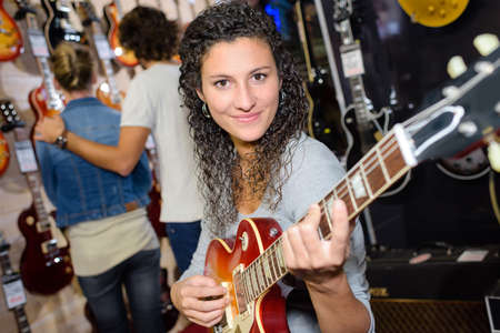smiling female customer trying to play guitar in store Stock Photo