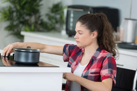 disabled young woman in wheelchair cooking dinner Stock Photo