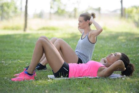 female friends doing sit ups outside in grass