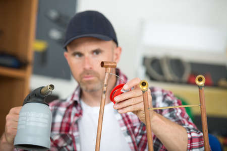 cooper: worker using blowtorch for soldering copper fittings