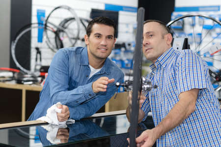 spokes: man checks a bike before buying in the sports shop