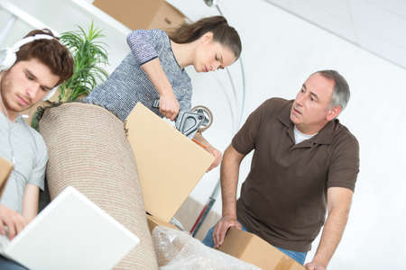 woman and father packing boxes and his lazy boyfriend