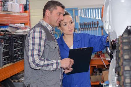 assessing: mechanic and cowoker assessing car