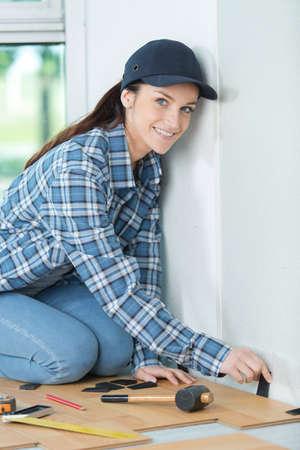 handywoman: beautiful young handywoman fitting floor boards
