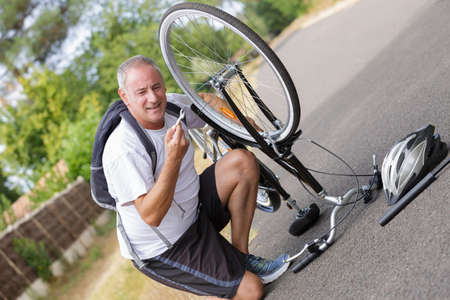 mature man is fixing his bike outdoors