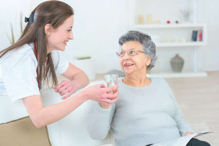 incapacity: caring nurse supporting her patient Stock Photo