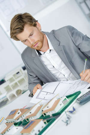 handsome architect working on a model in an office