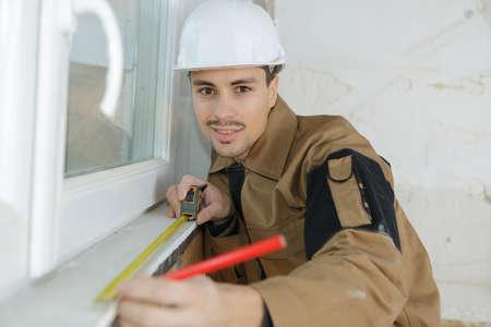 retractable: confident young builder measuring window
