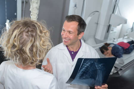 expected: doctors examining patients xray in hospital room Stock Photo
